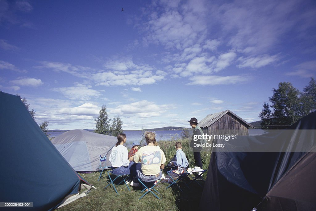 Group of people amongst tents in field, family with boy (10-11) : Stock Photo