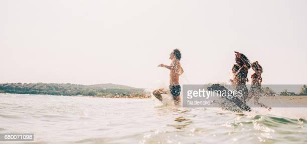 Grupo de personas y un perro nadando en el mar
