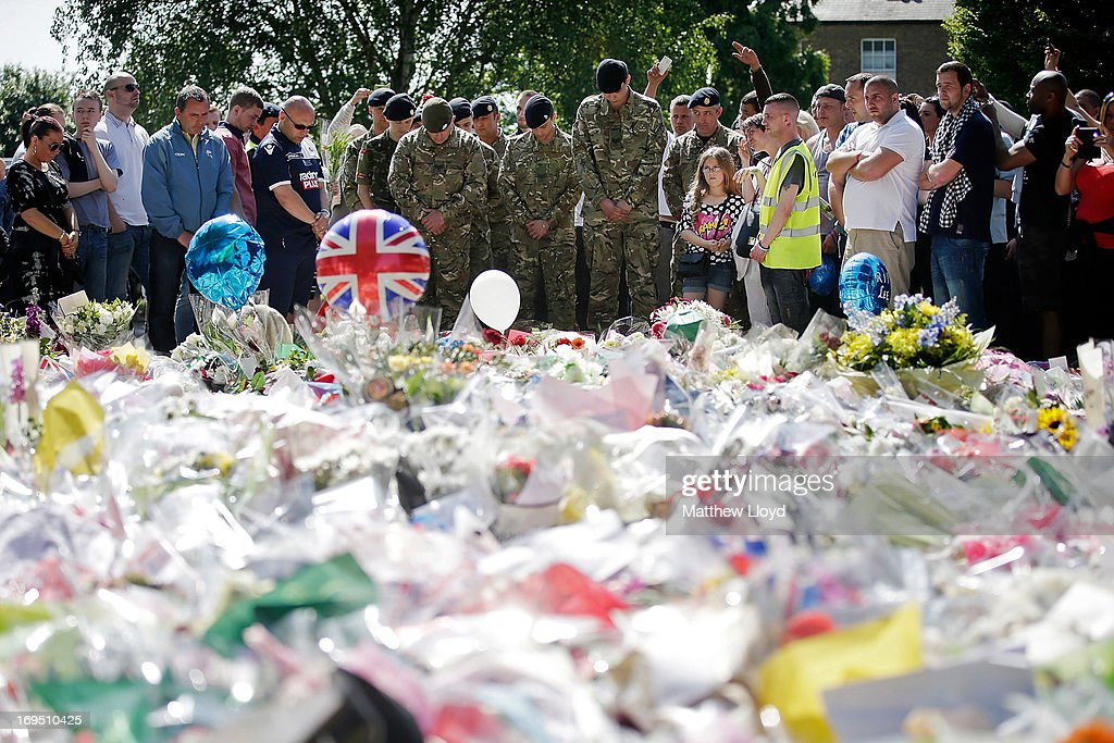 A group of people and soldiers gather outside the Royal Artillery Barracks, close to where Drummer Lee Rigby of the 2nd Battalion the Royal Regiment of Fusiliers was killed, on May 26, 2013 in London, England. Drummer Lee Rigby of the 2nd Battalion the Royal Regiment of Fusiliers was murdered by suspected Islamists near London's Woolwich Army Barracks. His family visited the scene of his murder today and left floral tributes whilst it was confirmed by the Foreign Office that one of the suspects, Michael Adebolajo, was arrested in Kenya in 2010.