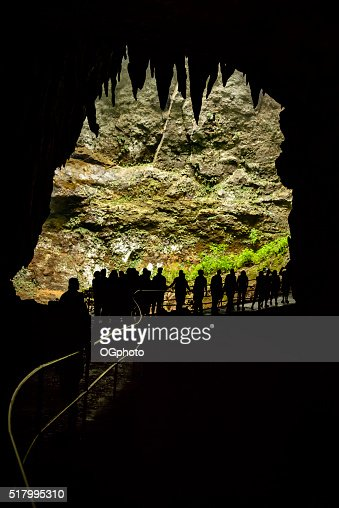 Group of people at a cave entrance. : Stock Photo