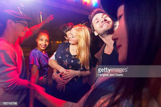 Group of people at party, man kissing woman's neck