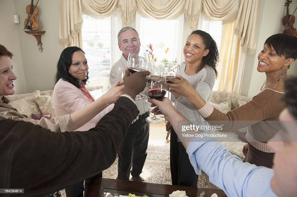 Group of people at party raising wine glasses : Stock Photo