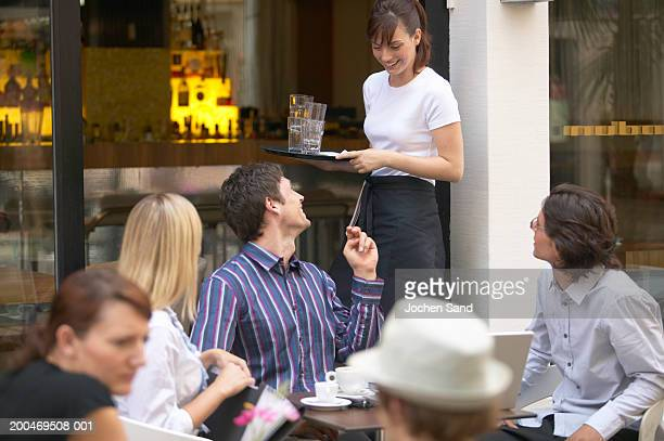 'Group of people at table outside bar, talking to waitress'