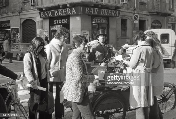 A group of people buying from an antique barrow interesting characters in Brera the Latin Quarter of Milan with its luxury restaurants and...