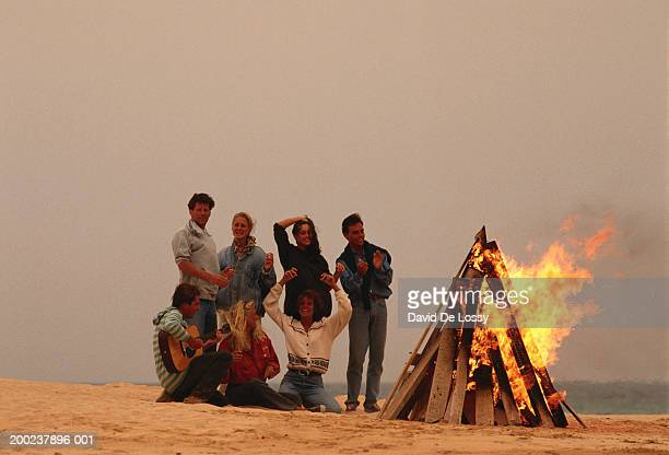 Group of people by campfire at beach