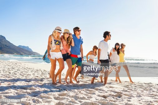 Group of people carrying cooler to party on beach : Stock Photo