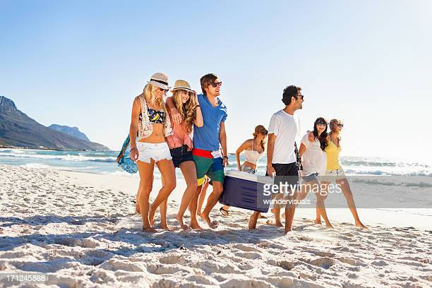 Group of people carrying cooler to party on beach