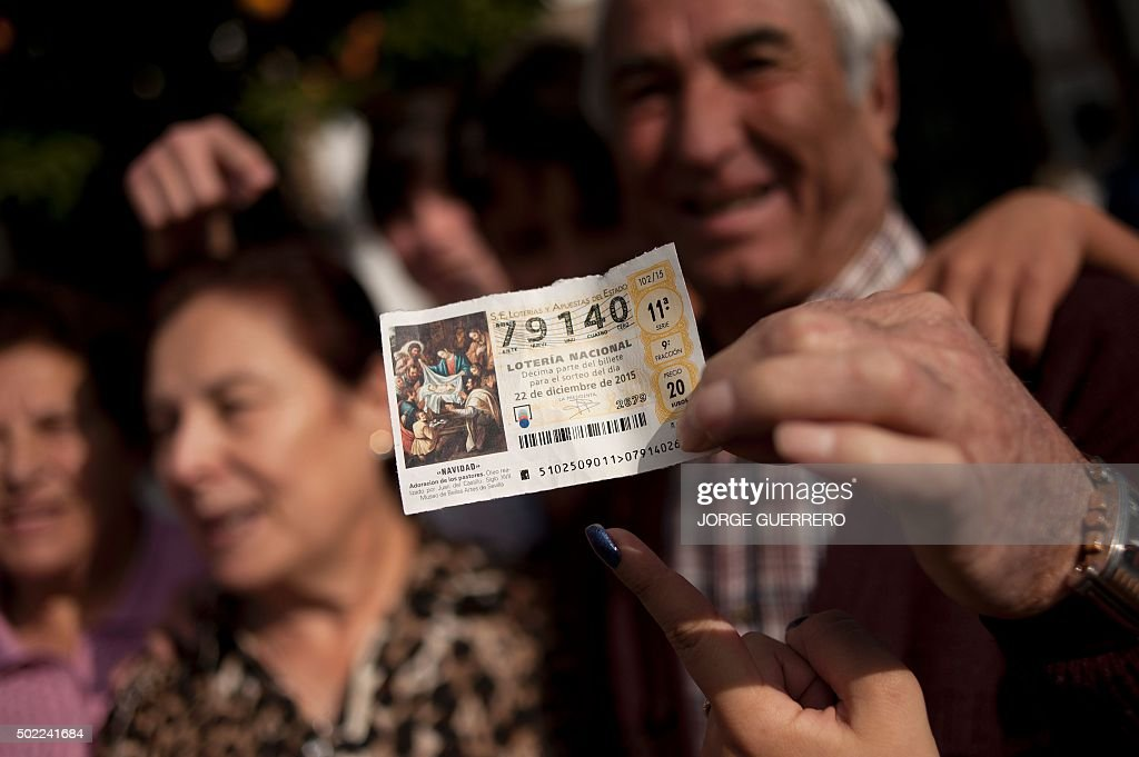 A group of people celebrate in a street of Villanueva de la Concepcion, near Malaga, as they hold a ticket wlth the first prize of the Spain's Christmas lottery named 'El Gordo' (Fat One) on December 22, 2015. This year's winning number is 79140 representing takings of 4 million euros (£2.9 million). The Gordo lottery first took place in 1812 in Cadiz and has not missed a year since, continuing through Spains civil war between 1936 and 1939. In 1938, there were actually two Christmas lotteries, one held in Burgos by dictator General Francos Nationalist regime, and the other in Republican-ruled Barcelona. AFP PHOTO / JORGE GUERRERO / AFP / Jorge Guerrero
