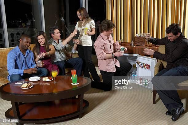 Group of people celebrating in hotel room, having drinks