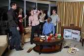 Group of people celebrating in hotel room, teenage boy (16-17) drinking from wine bottle