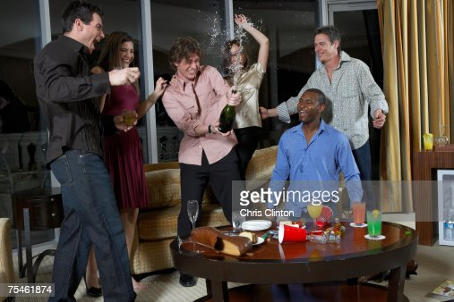 Group of people celebrating in hotel room, teenage boy (16-17) spraying champagne