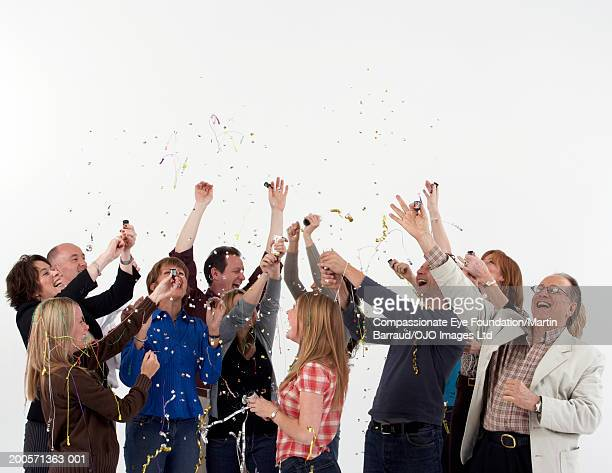 Group of people celebrating with party poppers