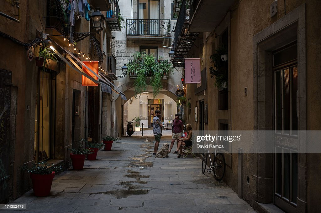 A group of people chat in a passage on July 24, 2013 in Barcelona, Spain. Foreign visitors to Spain set a new record high in June surpassing six million tourists for the first time ever and climbing by 5.3 percent since June 2012.