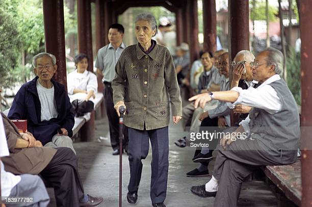 Group of people chatting and walking under a covered walkway at a Buddhist temple compound Wenshu Temple Chengdu Sichuan Province China
