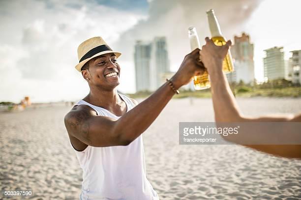 Gruppe von Menschen Jubeln Bier in der Dämmerung am Strand