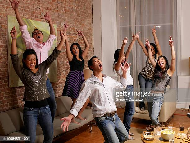 Group of people cheering in room