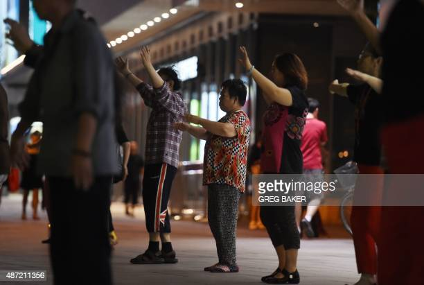 A group of people dance near a residential compound in Beijing on September 7 2015 A spate of noisy disputes between middleaged women and nearby...