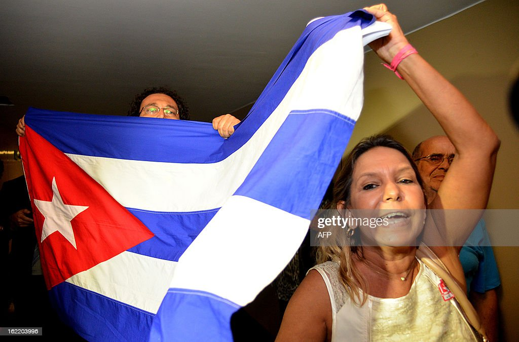 A group of people demonstrate against dissident Cuban blogger Yoani Sanchez as she arrives at the National Congress in Brasilia, on February 20, 2013. Sanchez is on an 80-day tour, after she got a passport two weeks ago under Cuba's sweeping immigration reform that went into effect this year. The 37-year-old philologist, who found an international audience on the Internet with her prize-winning blog 'Generation Y,' is known for her biting commentary, which has drawn the displeasure of Cuba's ruling communist party. AFP PHOTO/Pedro LADEIRA