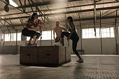 Group of people jumping on wooden boxes in gym.  Three people performing box jumping workout in health club.