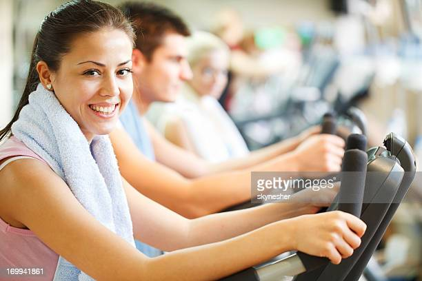 Group of people doing spinning in modern gym.