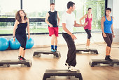 Group of people doing Step aerobics in the gym