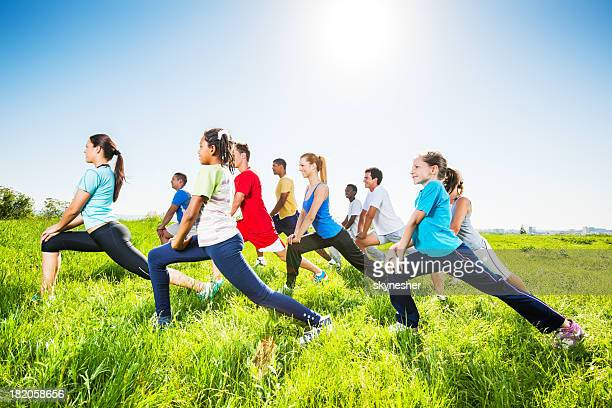Group of people doing stretching exercises in field