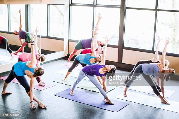 Group of people doing yoga class in a studio
