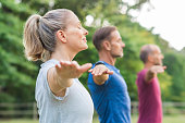 Group of senior people with closed eyes stretching arms at park. Happy mature people doing yoga exercise outdoor on a bright morning. Yoga class with woman and men doing breath exercising with stretch