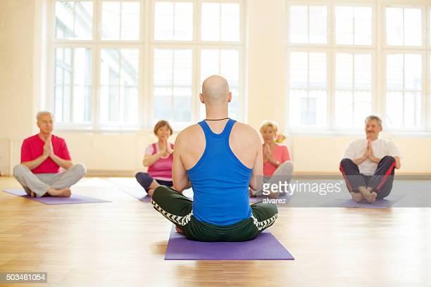 Grupo de pessoas a praticar yoga com Instrutor
