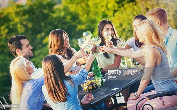Group of people drinking wine outdoors.