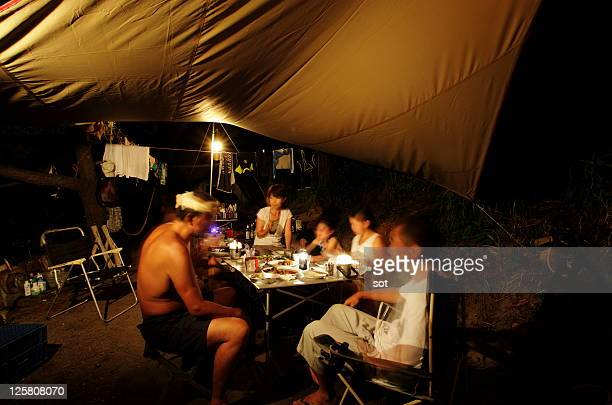Group of people eating dinner in tent at night