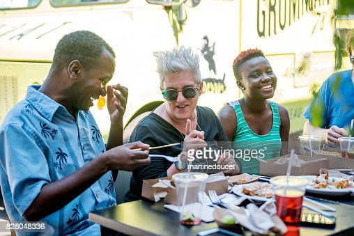 Group of people eating lunch from a food truck in a park. : Stock Photo