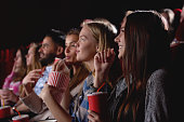 Group of female friends laughing and smiling watching a film together at the movie theatre snacks popcorn entertainment people lifestyle leisure friendship concept.
