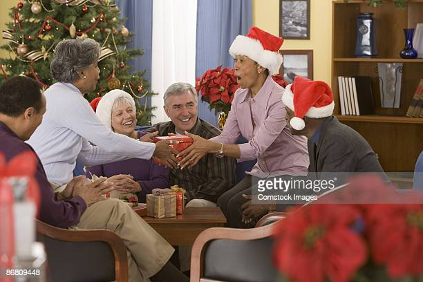 Group of people exchanging gifts at a christmas party