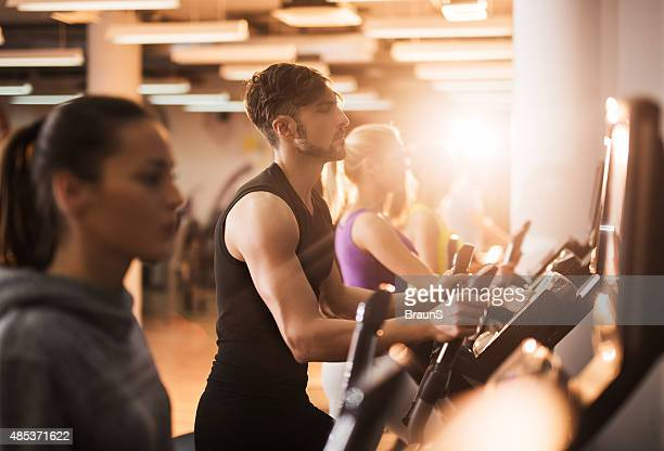 Group of people exercising on exercise machine in a gym.