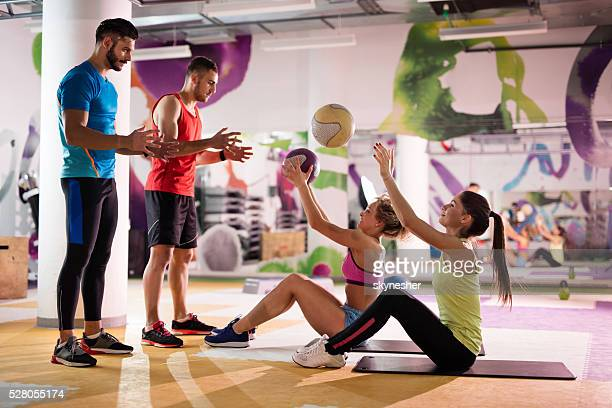 Group of people exercising with balls in a gym.