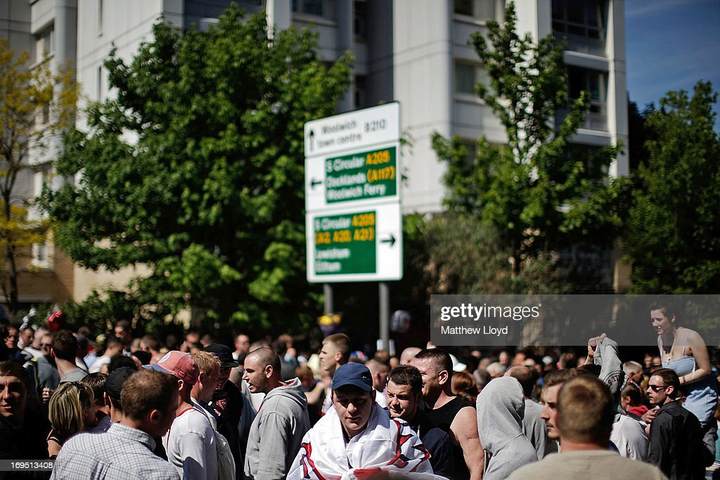 A group of people gather at the street sign where Drummer Lee Rigby of the 2nd Battalion the Royal Regiment of Fusiliers was killed, before marching to the Royal Artillery Barracks at Woolwich in a show of support on May 26, 2013 in London, England. Drummer Lee Rigby of the 2nd Battalion the Royal Regiment of Fusiliers was murdered by suspected Islamists near London's Woolwich Army Barracks. His family visited the scene of his murder today and left floral tributes whilst it was confirmed by the Foreign Office that one of the suspects, Michael Adebolajo, was arrested in Kenya in 2010.
