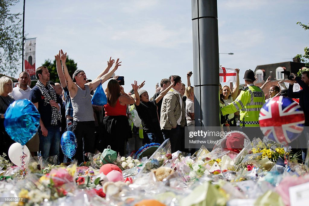 A group of people gather to chant and lay floral tributes outside the Royal Artillery Barracks, close to where Drummer Lee Rigby of the 2nd Battalion the Royal Regiment of Fusiliers was killed, on May 26, 2013 in London, England. Drummer Lee Rigby of the 2nd Battalion the Royal Regiment of Fusiliers was murdered by suspected Islamists near London's Woolwich Army Barracks. His family visited the scene of his murder today and left floral tributes whilst it was confirmed by the Foreign Office that one of the suspects, Michael Adebolajo, was arrested in Kenya in 2010.