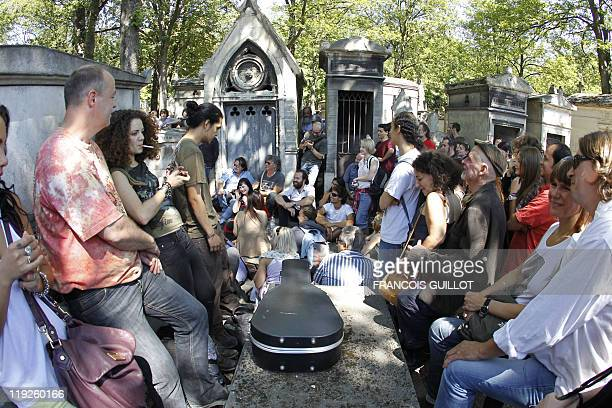 A group of people gather to pay homage on July 3 in front of US singer Jim Morrison's tomb at the Pere Lachaise cemetery in Paris 40 years after...