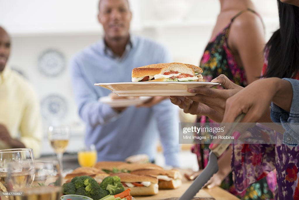 A group of people gathering for a party and a meal. An informal office party or networking social event. People handing plates of food across a buffet table.