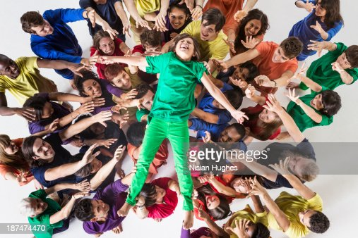 Group of People Happily Lifting Up a Young Boy : Stock Photo