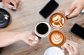 Group of people having a meeting after successful business negotiation in a coffee shop.Drinking hot beverage latte art coffee