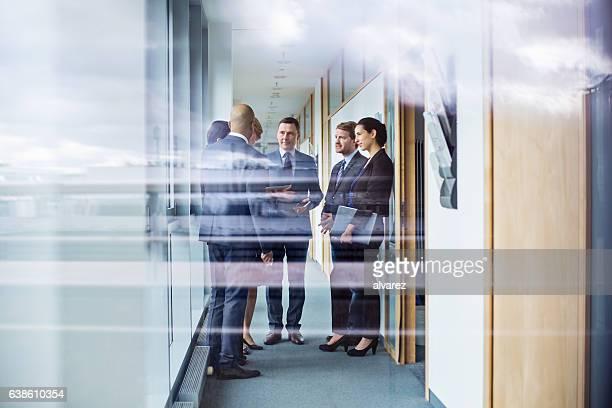 Group of people having business meeting in corridor