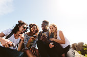 Young group of people sitting on top of mountain using smart phones and smiling. Diverse friends enjoying a day out.