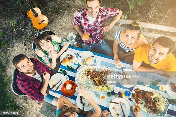 Groupe de personnes ayant un déjeuner en plein air.