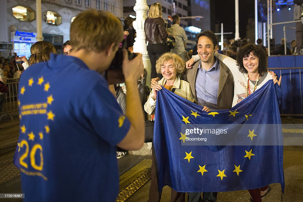 A group of people hold a European Union (EU) flag as they pose for a photograph during celebrations in Ban Jelacic square as Croatia marks it's entry into the European Union (EU) in Zagreb, Croatia, on Sunday, June 30, 2013. Croatia will become the European Union's 28th member at midnight, the bloc's first addition since Bulgaria and Romania joined in 2007. Photographer: Simon Dawson/Bloomberg via Getty Images