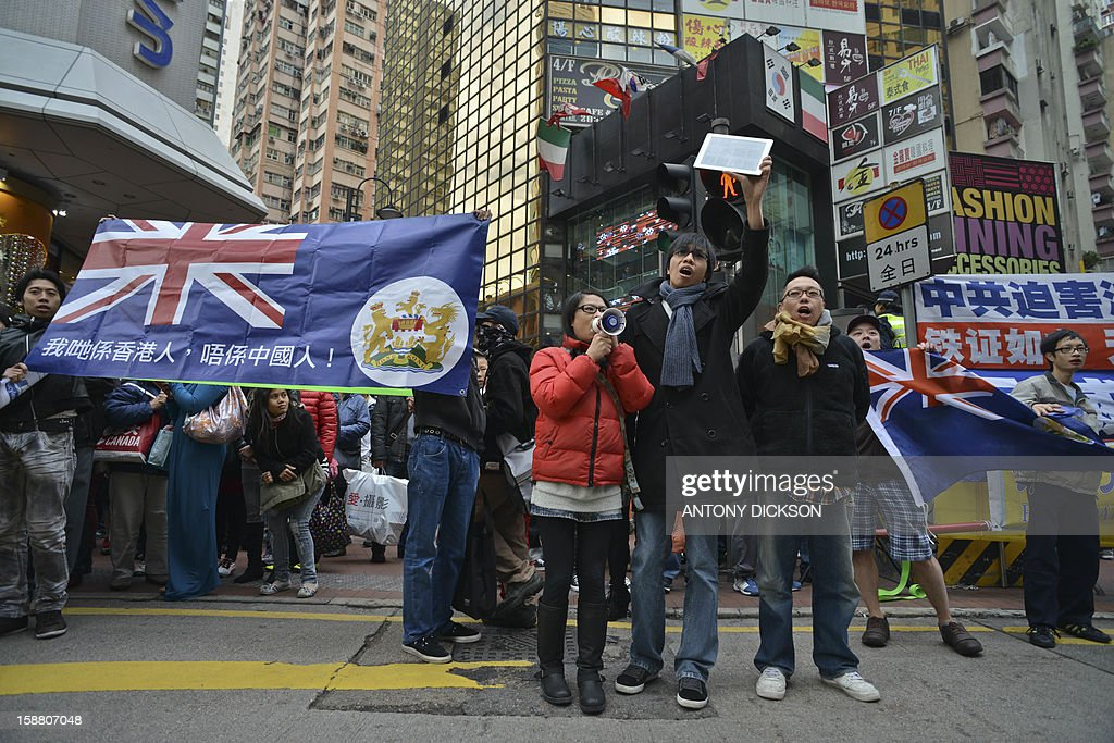 A group of people hold Hong Kong's former navy blue colonial flag shout slogans as marchers (not pictured) referring to themselves as supporters of Hong Kong and of the city's leader, Leung Chun-ying, walk though the streets of Hong Kong on December 30, 2012. Scuffles broke out during a march held by a Hong Kong pro-government group, two days ahead of a planned mass anti-government rally for New Year's day. AFP PHOTO / Antony DICKSON