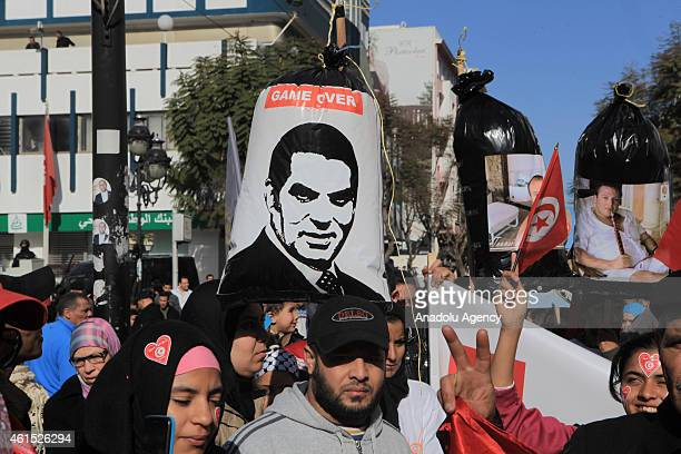 A group of people hold the posters of former President of Tunisia Zine El Abidine Ben Ali during a demonstration at the celebration of the 4th...