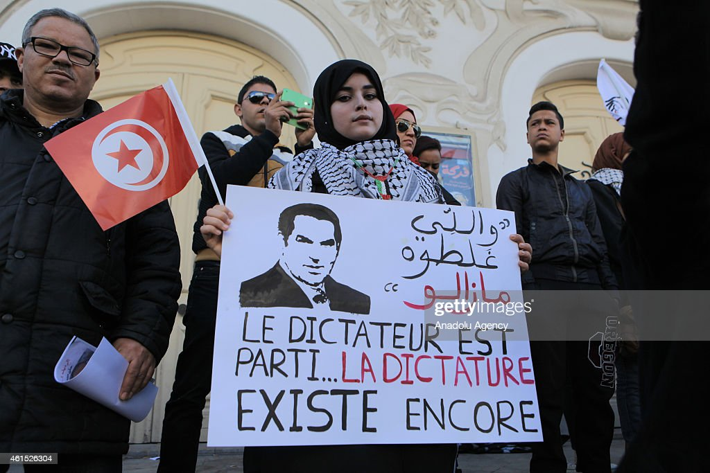 A group of people hold the posters of former President of Tunisia <a gi-track='captionPersonalityLinkClicked' href=/galleries/search?phrase=Zine+El+Abidine+Ben+Ali&family=editorial&specificpeople=598987 ng-click='$event.stopPropagation()'>Zine El Abidine Ben Ali</a> during a demonstration at the celebration of the 4th anniversary of the January 14 revolution at Avenue Habib Bourguiba in Tunis capital of Tunisia on January 14, 2015.