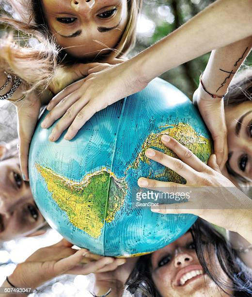 Group of People Holding a Globe